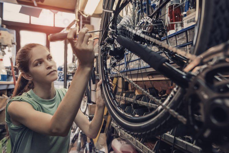 kobieta naprawia koła od roweru