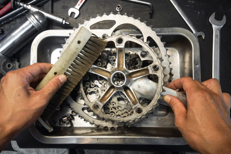 mężczyzna czyści łańcuch od roweru