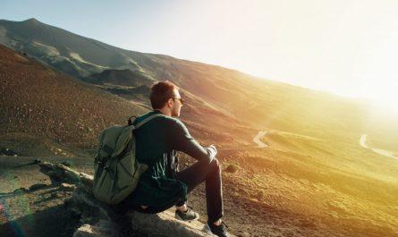 mężczyzna-z-plecakiem-siedzi-na-skale-w-górach