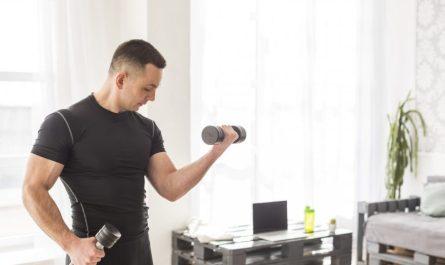 umięśniony mężczyzna ćwiczy bicepsy z hantlami