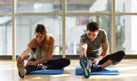 mężczyzna-i-kobieta-rozciągają-się-siedząc-na-matach-w-siłowni