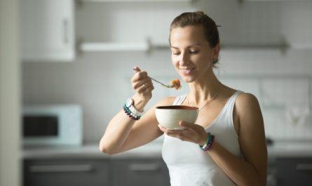zdrowa kobieta je rybe widelcem z miski
