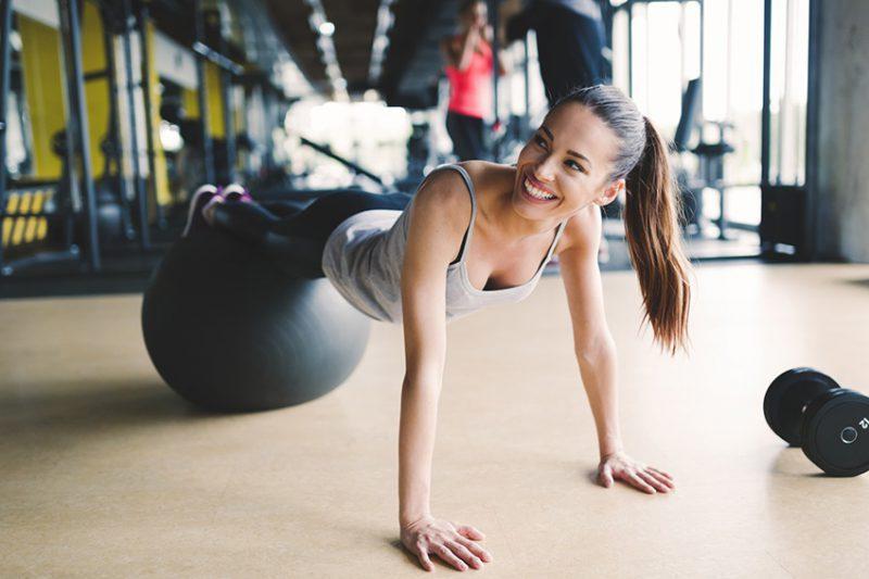 kobieta ćwiczy na piłce w siłowni