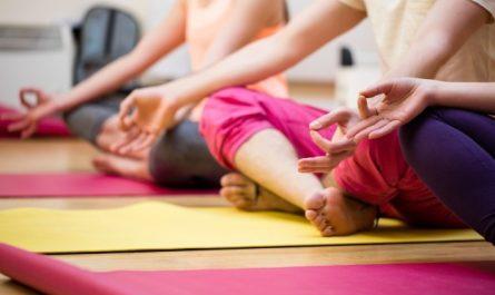 kobiety wykonuje cwiczenia z jogi na sali gimnastycznej
