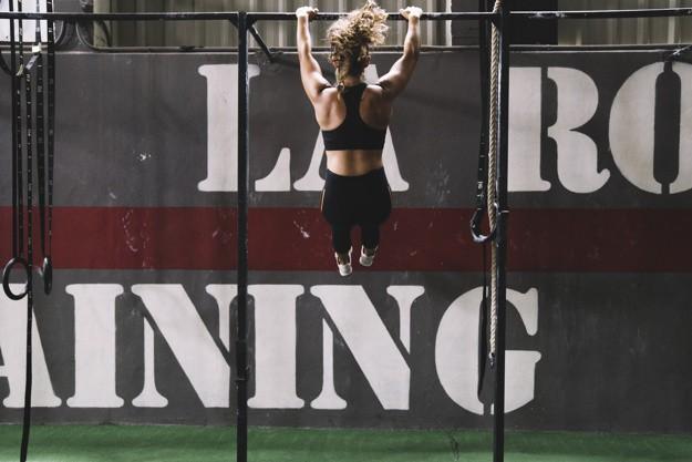 kobieta wykonuje muscle upy na drazku