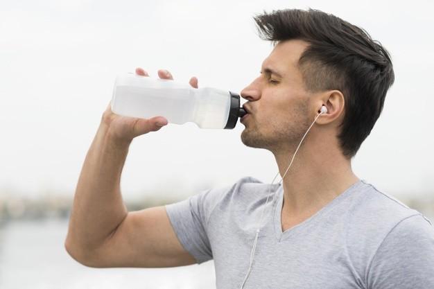 biegacz pije napoj izotoniczny