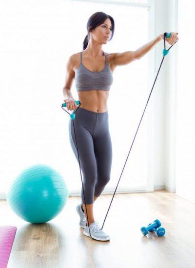 kobieta robi cwiczenia z gumami na ramiona