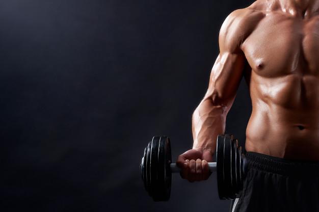 mezczyzna robi biceps hantlami