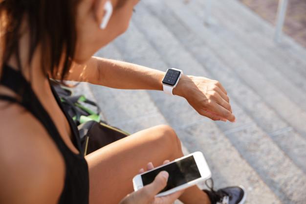 kobieta ustawia zegarek sportowy