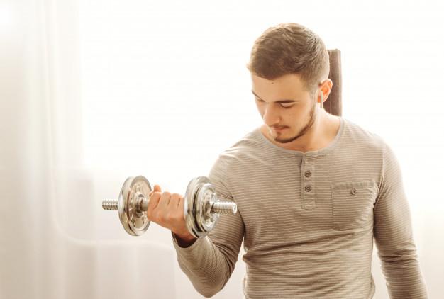 mezczyzna trenuje biceps w domu